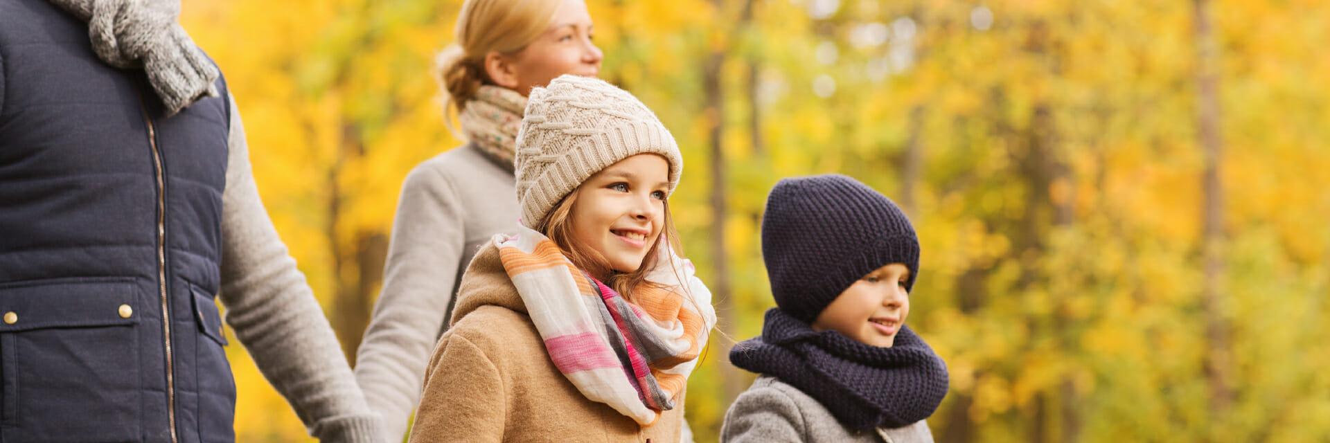 Famille qui marche avec les feuilles d'automne