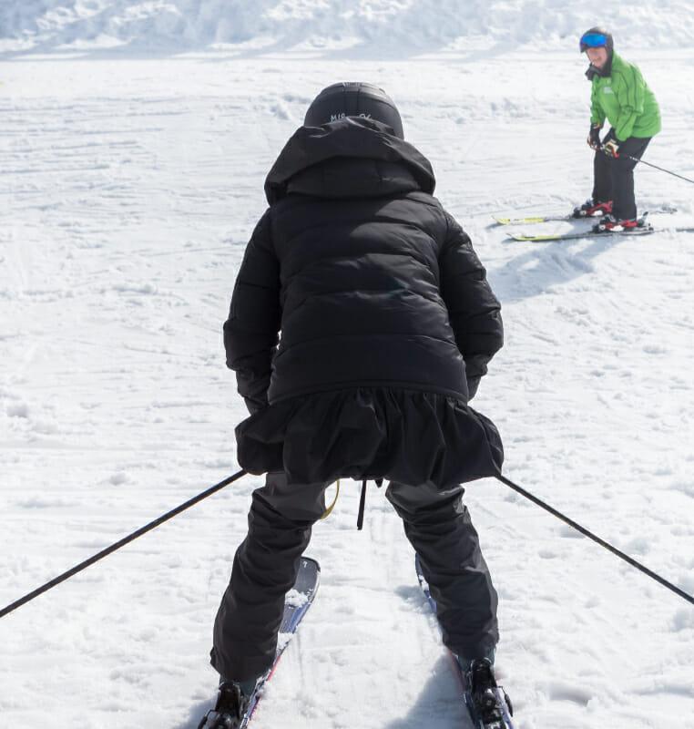 femme de dos en chasse-neige en ski