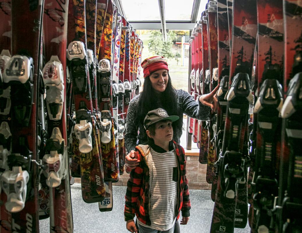maman et son fils qui regardent les skis à vendre
